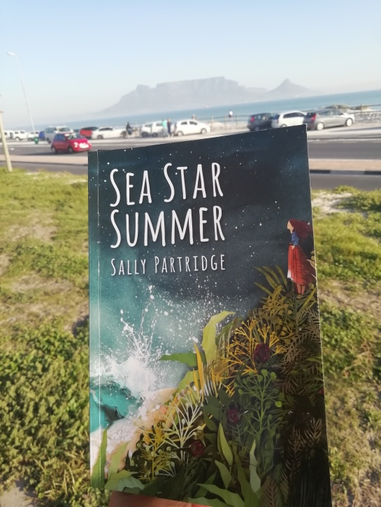 The book Sea Star Summer with green grass, blue skies and Table Mountain in the background.